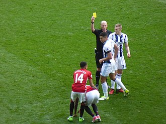 Mike Dean (referee) - Dean brandishing a yellow card in a match between Manchester United and West Bromwich Albion in April 2017.