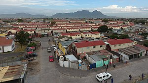 Manenberg - A view of Manenberg looking towards Table Mountain in the background.  The red roofed government housing blocks in-which a large proportion of the community's population lives can be seen in the foreground.