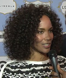 A woman with curly black hair is talking into a microphone.