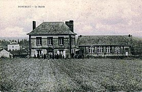 Carte postale noir et blanc représentant deux bâtiments en arrière-plan et un champ au premier plan.