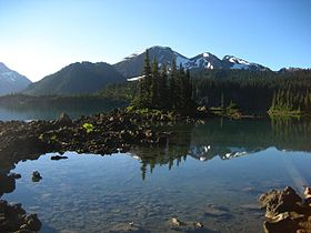 A lightly glaciated mountain rising above trees and a lake in the foreground.
