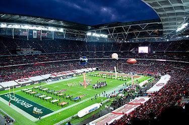 Фотография лондонского стадиона Уэмбли во время церемонии открытия международной серии NFL 2010, на которой видно поле и трибуны, заполненные болельщиками.