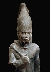 Statue of a standing pharaoh in black stone. He is holding a mace and a rounded crown.