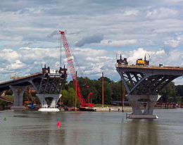 Two level metal structures on concrete supports on either side of a river. There is construction equipment on both of them and a large red crane on the far shore