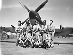 Black and white photograph of eight men wearing military uniforms posing in front of the nose of a single engined monoplane propeller fighter aircraft.