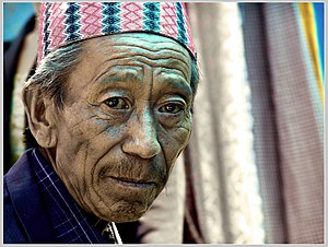 Man with deep wrinkles and a round cap at Rava...