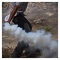 Palestinian Demonstrator picks Tear gas grenade to throw back Kafr Qaddum August 2014.jpg