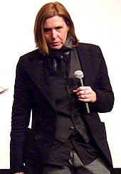 A female musician, Patty Schemel, wearing a black suit and holding a microphone.