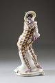 Porslinsfigur från 1910-talet klädd i rutig harlekindräkt bärande en markatta - Hallwylska museet - 93837.tif