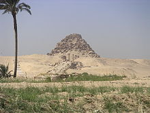 Photograph of the eroded remains of a pyramid with the remaining complex laid out before it