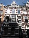 foto van Herenhuis in neo-renaissance trant, gedateerd in cartouches in de ontlastingsbogen. Middentopgevel met rolwerkvoluten, obelisken en aedicula. Versiering met banden. Houten erker op voluutconsoles