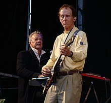 Krieger performing guitar onstage in front of Manzarek, seated at a keyboard