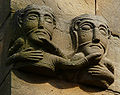 Rosheim, Romanesque sculpture, busts of men holding each other by the beard.jpg