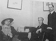 A photograph of a seated woman and man in front of a desk with a standing man behind them and to the right.