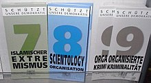 "Display with three types of information leaflets, with the numbers and titles ""7 Islamischer Extremismus"" (coloured in shades of green), ""8 Scientology Organisation"" (coloured in shades of blue) and ""9 Organisierte Kriminalität"" (shades of grey). At the top of each leaflet is the inscription ""Schützt unsere Demokratie""."