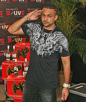 A man saluting with his right hand and wearing a black graphic T-shirt and black jeans. In the background is a palm tree, a few bottles of rum, and a screen with branding across it.