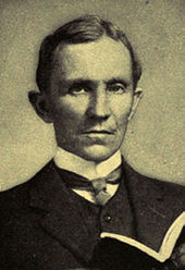 Man, probably mid-forties, dark hair, clean shaven, wearing a high collar with tie, looking staright ahead. He is holding an open book
