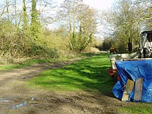A straight muddy path leads through a small clearing filled with farming equipment.