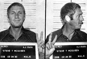 V sign - American actor Steve McQueen flashing the V sign for a mugshot, after being arrested for drunk driving.
