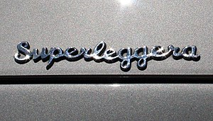 Superleggera - Superleggera emblem on an Aston Martin DB5, with a body manufactured by Carrozzeria Touring, the firm that originated the superleggera system.