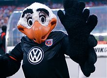 A black and white costumed bald eagle mascot with exaggerated features and an orange beak raising his wings. He wears a black soccer jersey with a white Volkswagen logo and the team's shield on it.