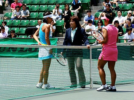 An umpire informing two players of the rules Tennis umpire.jpg