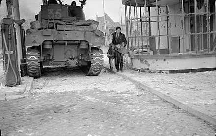 A Dutch civilian lifts his two children away from danger near a Sherman tank during fighting in Hertogenbosch The British Army in North-west Europe 1944-45 B11382.jpg