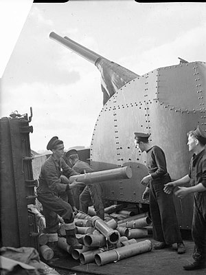 Battle of the Bay of Biscay - Sailors aboard HMS Glasgow clear cartridge cases ejected from the twin 4 inch Mark XVI guns