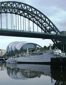 An iron bridge with a semi-circular upper structure, over the river Tyne. Beneath the bridge is a large white boat with several decks.