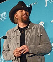 A bearded man wearing a grey shirt and a black cowboy hat