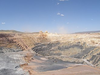 Open-pit mining - Rock blasting at the large open-pit Twin Creeks gold mine in Nevada, United States. Note the size of the excavators for scale (foreground, left), and that the bottom of the mine is not visible.