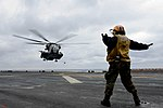 U.S. Navy Aviation Boatswain's Mate (Handling) 3rd Class Elizabeth Blasco directs a CH-53E Super Stallion helicopter onto the flight deck of the amphibious assault ship USS Bataan (LHD 5) in the Aegean Sea 140310-N-JX484-115.jpg