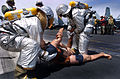 US Navy 040529-N-6213R-029 A flight deck Crash and Salvage crew move Oscar the training manikin to safety during a recent flight deck fire and barricade drill held aboard USS John C. Stennis (CVN 74).jpg