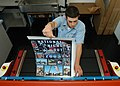 US Navy 050829-N-4385W-008 Photographers Mate Airman Jesse Praino laminates a poster for the National Night Out Program.jpg