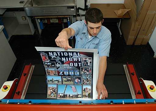 US Navy 050829-N-4385W-008 Photographers Mate Airman Jesse Praino laminates a poster for the National Night Out Program