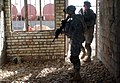 US Navy 060313-N-6901L-012 Two U.S. Army soldiers assigned to the 66th Armor Regiment, Alpha Company, search an abandoned building to make sure it is safe before conducting business with nearby locals.jpg