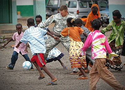 US Navy 061202-N-1328C-114 U.S. Army Staff Sgt. Justin Lockhart, attached to Bravo Co., 489th, Civil Action Battalion, participates in a game of soccer with students from the Djibouti City School.jpg