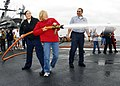 US Navy 070826-N-1513W-071 Operations Specialist 2nd Class Heather McAfee and her mother receive firefighting instructions from Damage Controlman 2nd Class Gilbert Sandum during a damage control olympics display for friends and.jpg