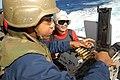 US Navy 080205-N-6326B-028 Gunner's Mate 2nd Class Rodolfo Jasso, right, teaches Aviation Ordnanceman Airman Travis Jackson how to load and fire a .50-caliber machine gun.jpg