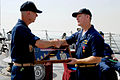 US Navy 080603-N-0924R-031 Command Master Chief Gregg Snaza presents Cmdr. Paul Stader with a shadow box during change of command ceremony aboard the guided-missile destroyer USS Ross (DDG 71.jpg