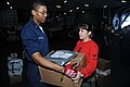 US Navy 090104-N-2908M-004 Postal Clerk 3rd Class Justin Richard gives mail to Aviation Ordnanceman 3rd Class Ivianna Ortiz during mail call.jpg