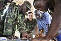 US Navy 100818-N-7589W-331 Boatswains' Mate 2nd Class Daniel Mendoza watches as Sierra Leone soldiers plot a navigational course during a two-week small craft operations training exercise.jpg