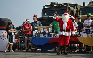 US Navy 111225-N-GH121-031 Chief Damage Controlman Alan Vanmarter, dressed as Santa Claus, passes out gifts during a holiday gift event for Sailors.jpg