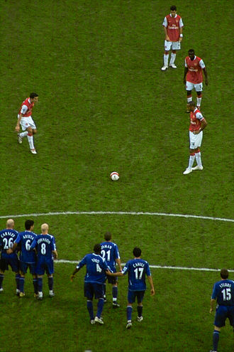 Direct free kick - Often several players (red) will line up for a free kick, so as to mask their intentions to the defending team (blue).