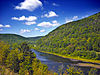 A river curves between two forested mountains under a bright blue sky with a few clouds