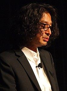 Porträt von Yoshio Sakamoto, der eine öffentliche Rede hält.