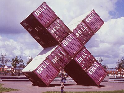 large-scale arrangement of red cuboid shipping containers in the shape of a letter X on display in a park with trees in the background. People walking underneath.