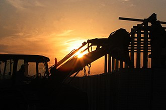1st Marine Logistics Group - A U.S. Marine with Operations Platoon, Engineer Company, Combat Logistics Battalion 5, 1st Marine Logistics Group (Forward) directs a backhoe – building barriers to guard a checkpoint near Fallujah, Iraq. (December 2006, USMC photo)