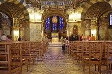 Photographie de l'intérieur d'une chapelle de style roman avec un large lustre doré suspendu au-dessus d'un autel.