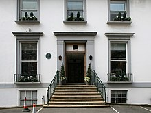 A flight of stone steps leads from an asphalt car park up to the main entrance of a white two-story building. The ground floor has two sash windows, the first floor has three shorter sash windows. Two more windows are visible at basement level. The decorative stonework around the doors and windows is painted grey.